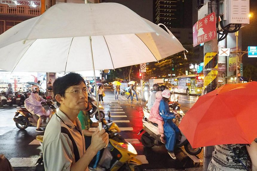 Pedestrians and motorcyclists wait at traffic light in the rain in Taipei, Taiwan, on July 7.