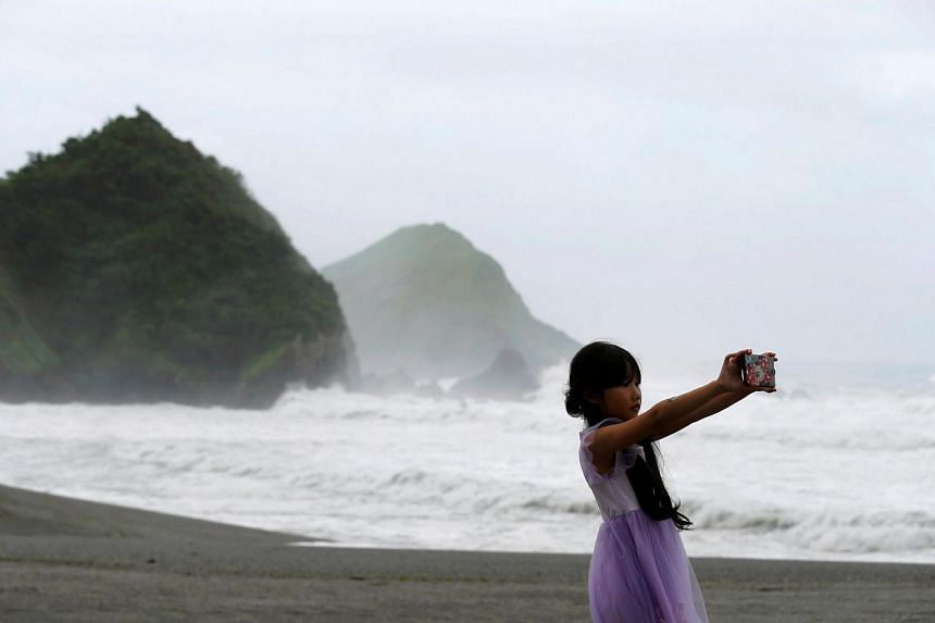 Waves are seen behind a girl as Typhoon Nepartak approaches, in Yilan, Taiwan, on July 7.