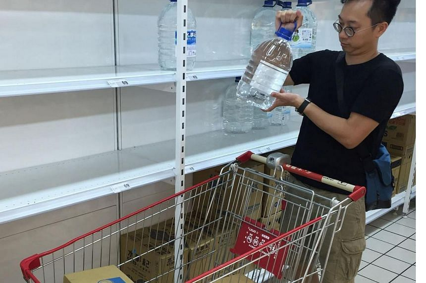 A man takes a big bottle of mineral water from a shelf at a hypermarket in Taipei on July 7.