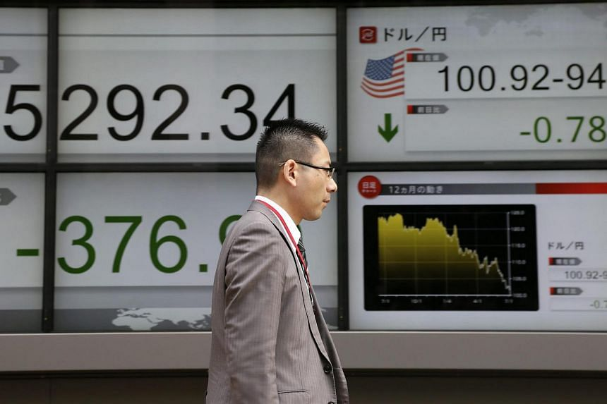 A businessman walks past a monitor displaying stock information in Tokyo, Japan, on July 6.