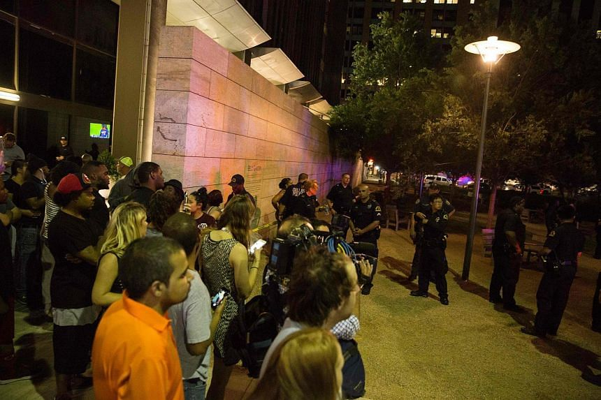 Protestors yell after police officers arrest a bystander following the shooting at a protest in Dallas on July 7.