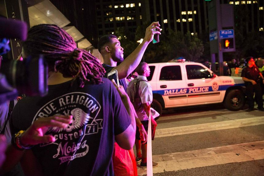Bystanders stand near police barricades following the sniper shooting in Dallas on July 7.