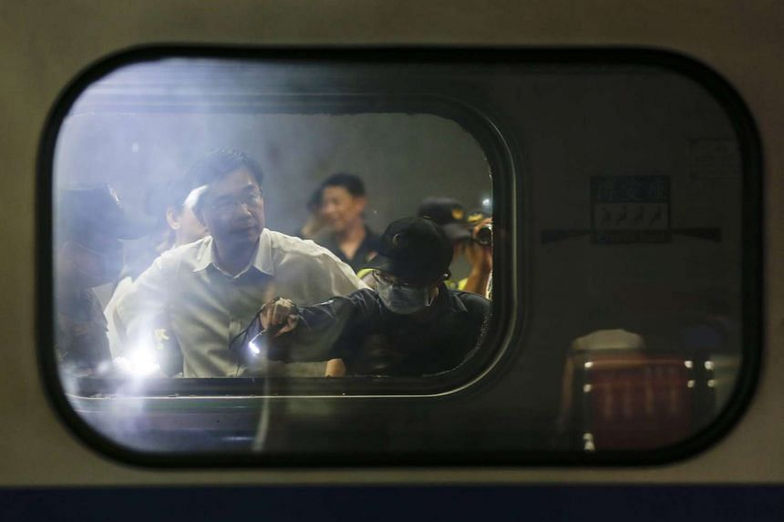 Taiwanese investigators inspect debris inside a train carriage after an explosion at Songshan train station in Taipei.