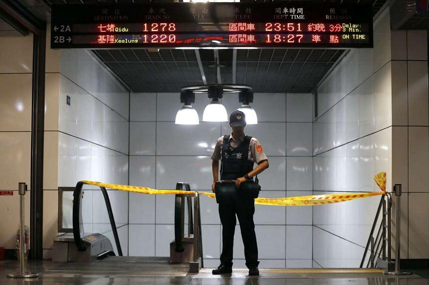 A Taiwanese police officer stands guard at the entrance after an explosion at Songshan train station in Taipei.