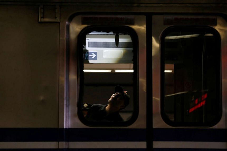A policeman is seen through the broken windows of a train after an explosion at the Songshan train station in Taipei, Taiwan, on July 7.