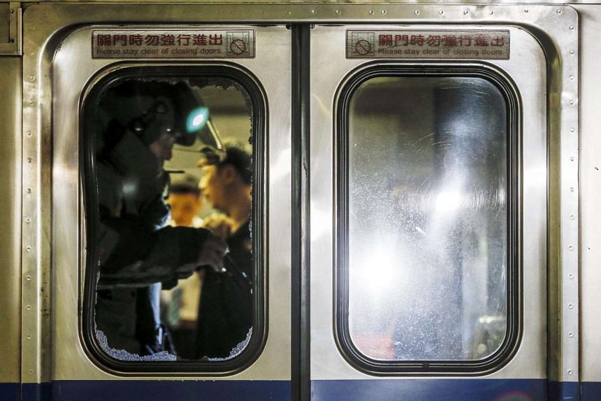 A member of a bomb squad is seen through a broken glass door of a train carriage after an explosion at Songshan train station in Taipei, Taiwan, on July 7.