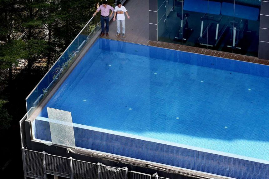 The glass panels on the outside of the infinity pool wall at Cradels condo in Whampoa fell from the fifth floor yesterday afternoon, sending water gushing down below.