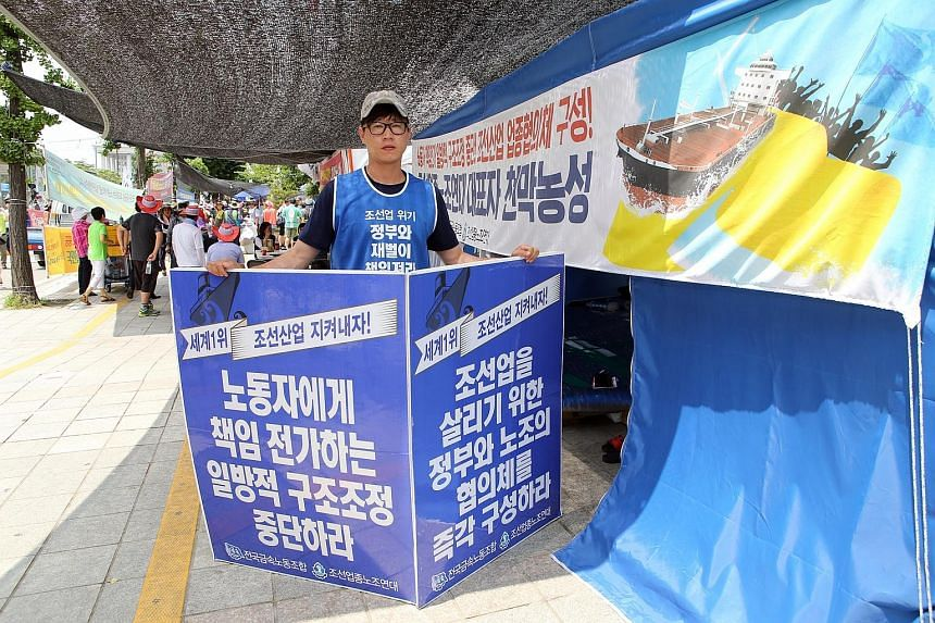 Mr Park, a shipyard electrician, has been protesting against the shipping crisis in front of South Korea's Parliament House since June 26. His sign calls for responsibility towards shipbuilding union members.
