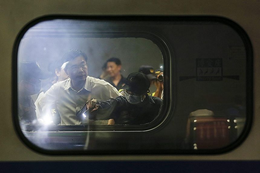 Above: Investigators inspecting the debris inside the train carriage at Songshan railway station after the blasts on Thursday. Left: A photo of a homemade explosive device found at the railway station.