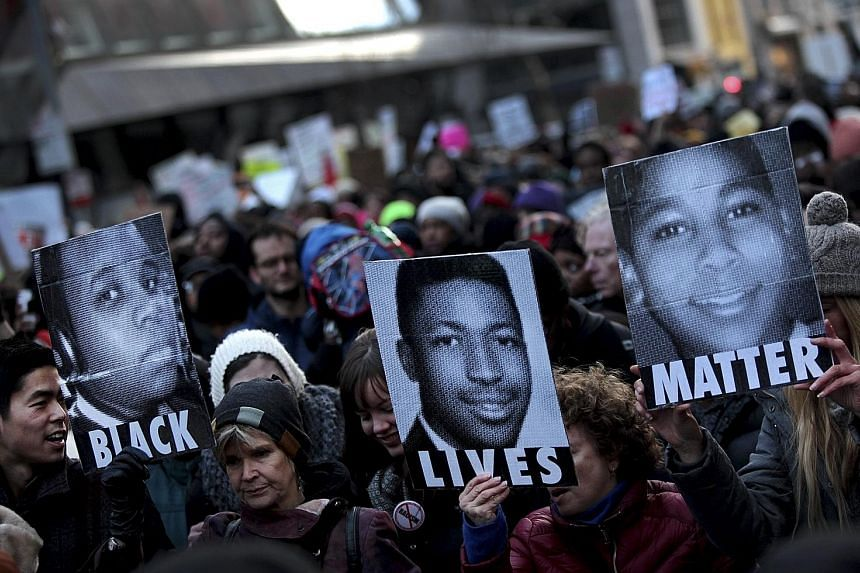 Demonstrators in New York holding posters of Michael Brown (from left), Eric Garner and Tamir Rice in December 2014, during a march to protest against their deaths.