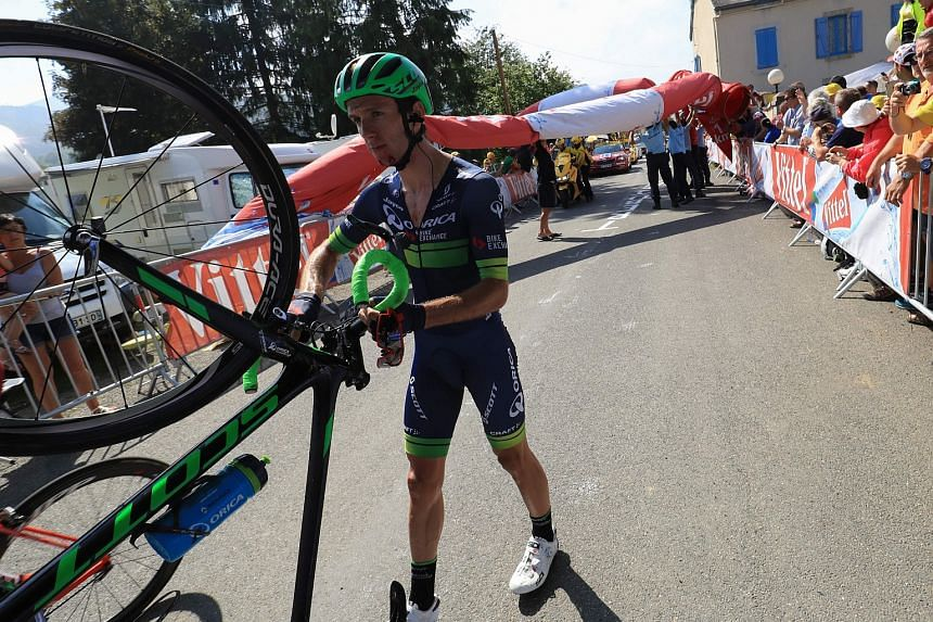 England's Adam Yates, injured after his fall, walks with his bicycle.