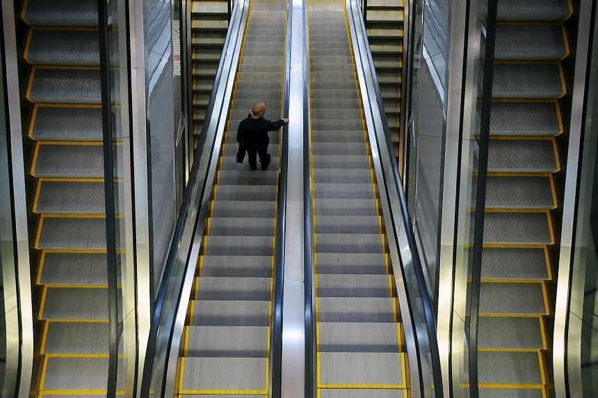 A man takes an escalator at a mall in Singapore in this September 14, 2011 file photo.