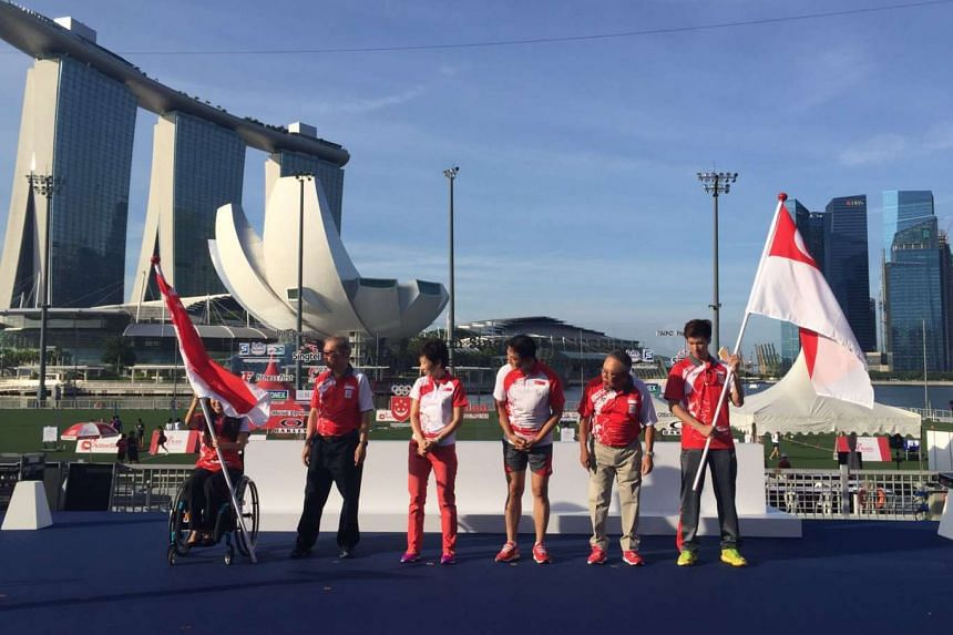 Shuttler Derek Wong and para-swimmer Yip Pin Xiu (carrying flags) will be the Olympic and Paralympic flagbearers respectively at the Rio games.