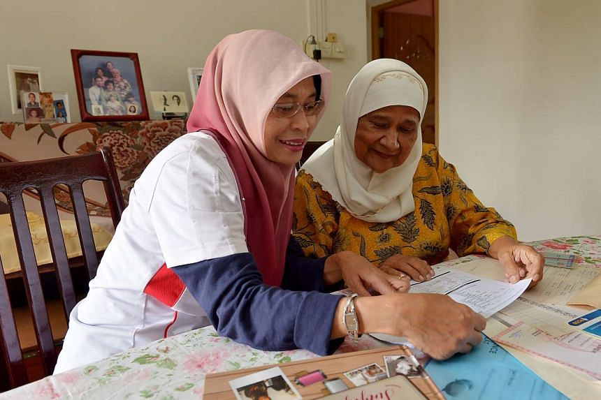 A coordinator for the Pioneer Generation (PG) Ambassadors programme explains the PG package to a senior citizen.