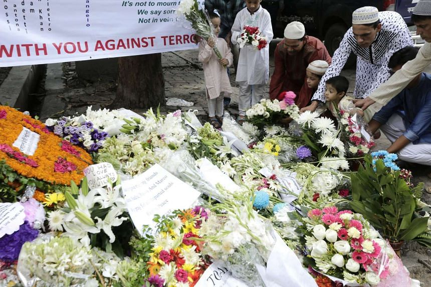 Victims' family members place flowers on July 7, 2016, to pay tribute to the victims of the July 1 Dhaka terror attack.