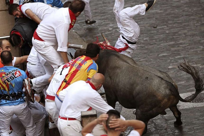 A bull gores a runner during the third bull run of the San Fermin festival in Pamplona, Spain, on July 9, 2016.