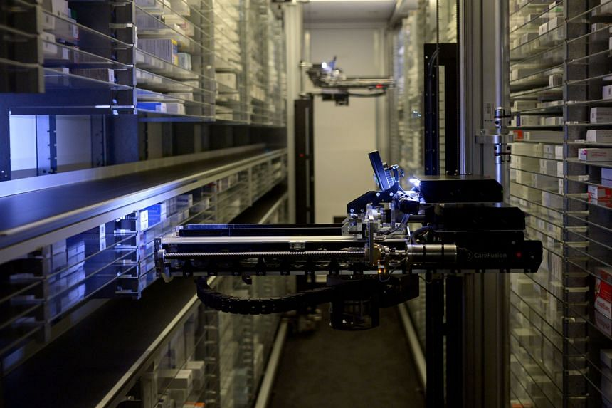 Above: A robotic arm in NUH automatically picking up and packing medicine at the pharmacy. The machine is part of the Outpatient Pharmacy Automation System that went live in November 2014.