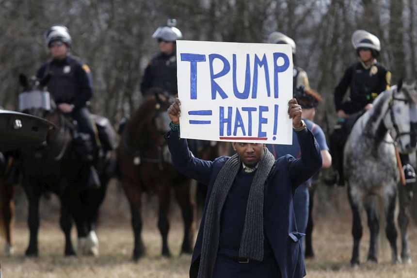 An anti-Trump protester holds his protest sign in front of mounted police outside a rally for Republican US. presidential candidate Donald Trump in Cleveland, Ohio, in March.