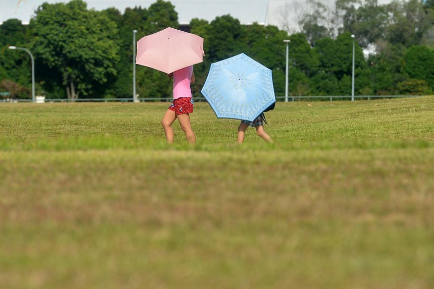 People carrying umbrellas to shield themselves from the blazing sun in Bishan central on April 2, 2016.