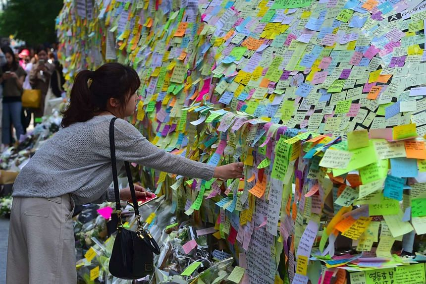 South Koreans leave messages written on post-it notes at an exit of Gangnam subway station, which has been turned into a mini shrine for a 23-year-old woman who was stabbed to death on May 20.