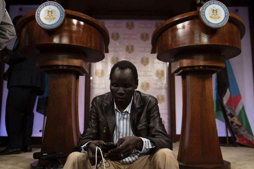 Journalists sit inside the conference room as artillery fire broke out near the presidential palace in Juba on July 8, 2016.