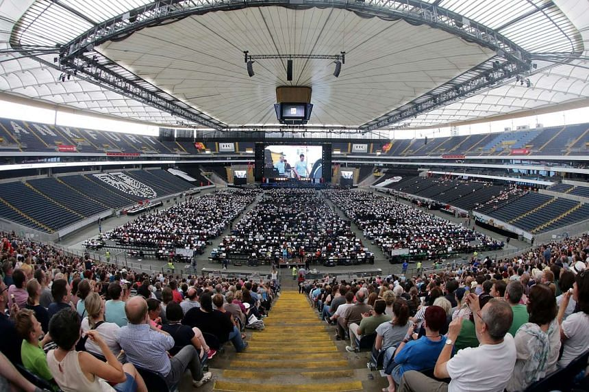 Spectators on the ranks of the Commerzbank Arena stadium watch members of a mass orchestra rehearsing in Frankfurt, Germany on July 9, 2016.