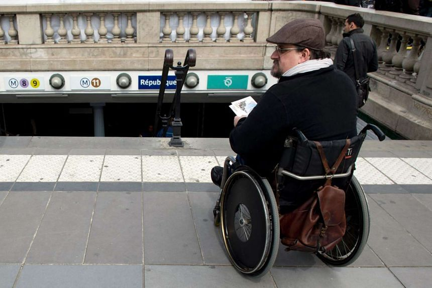 A disabled man in a wheelchair distributing flyers at the top of a metro station's stairs in Paris on May 13, 2014.