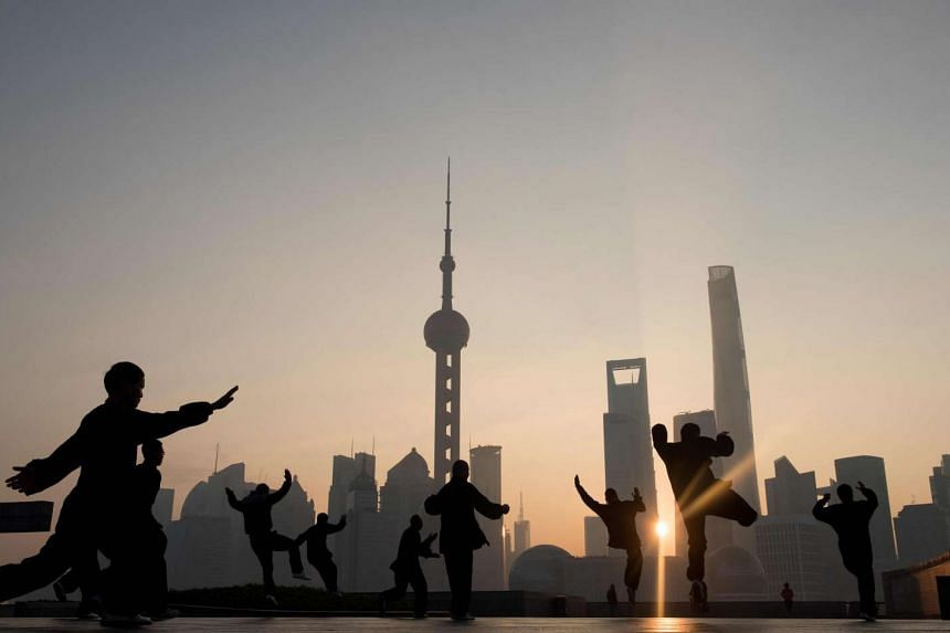 This file photo taken in 2015 shows people doing morning exercises in front of the skyline of the Lujiazui Financial District in Pudong in Shanghai.