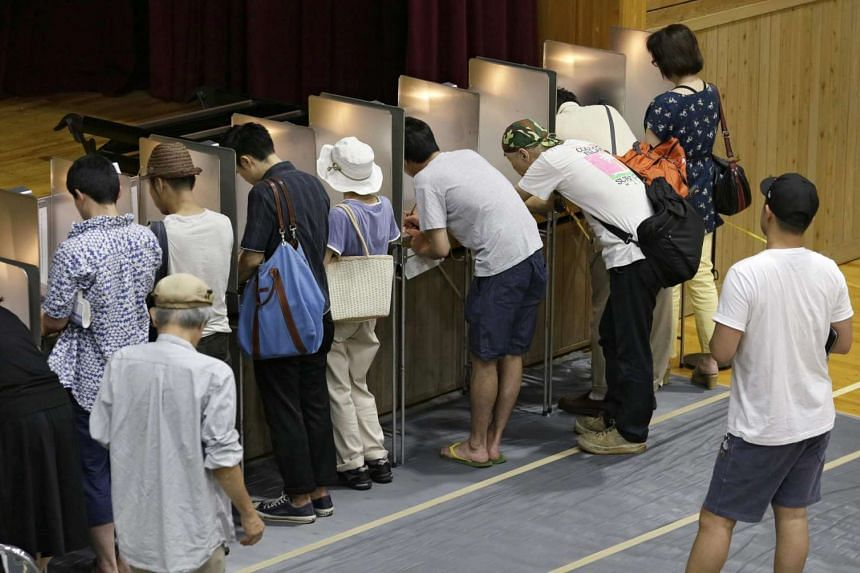 Voters fill their ballot papers for the Upper House election at a polling station in Tokyo, Japan on July 10, 2016.