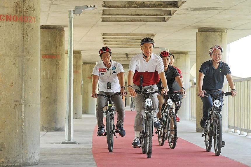 PM Lee, LTA chief executive Chew Men Leong (far right) and Dr Koh Poh Koon (behind, partially hidden), an MP for Ang Mo Kio GRC, taking a ride on the 4km-long cycling path that loops around Ang Mo Kio Avenues 1, 3 and 8. Cycling paths are painted red