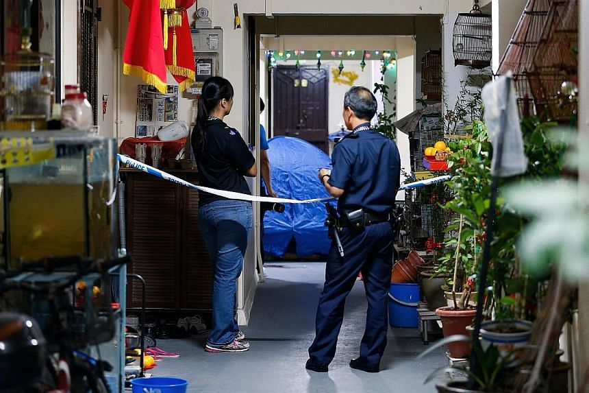 Police officers examining the area where a 52-year-old's bloody body was found near a coffee shop in Geylang Lorong 23 yesterday morning. The dead man was said to be a former helper at a stall in the coffee shop. In Yishun, a 26-year-old man was foun
