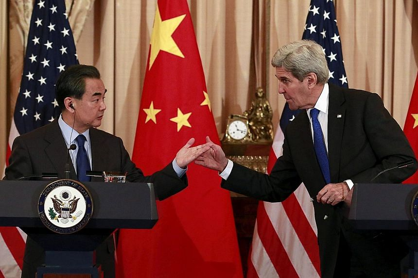 "China's Foreign Minister Wang Yi, in a phone call with United States Secretary of State John Kerry on Wednesday, labelled the case ""a farce that should be stopped"". They are seen here at a news conference in Washington in February, after a meeting at"