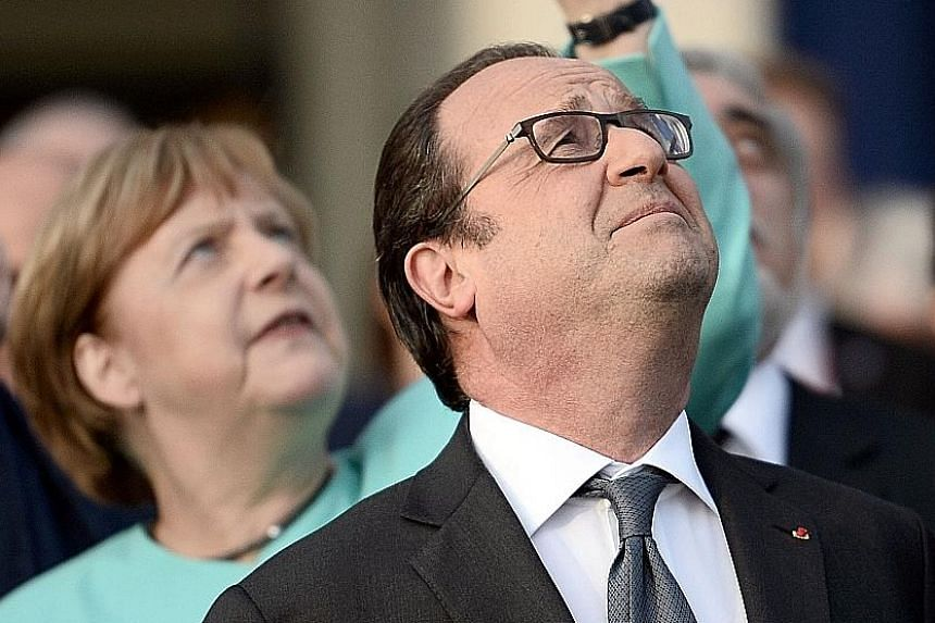 French President Francois Hollande and German Chancellor Angela Merkel at a fly-past of Nato countries' jet fighters at the summit in Warsaw, Poland, on Friday.