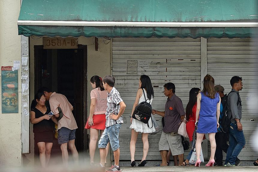 Sex workers used to be a common sight in Geylang (left) as they worked in brothels or plied the streets under the watchful eye of pimps (right). But the rise of the Internet has led to a new group of Geylang prostitutes - freelancers, who rent apartm
