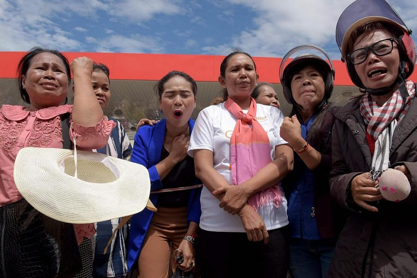 Cambodian women cry outside a convenience store where independent political and social analyst Kem Ley was shot dead in Phnom Penh on July 10.