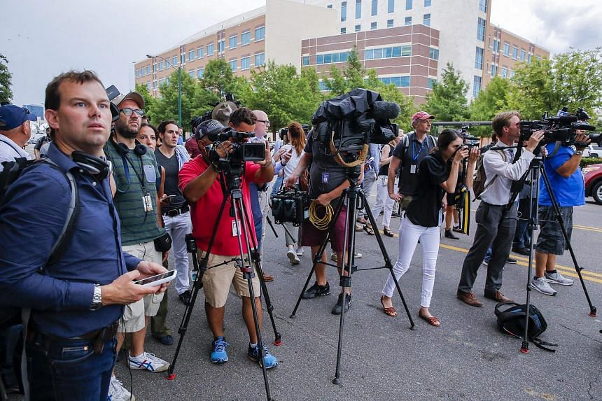 Members of the media watch as heavily-armed Dallas Police Department officers investigate a threat at the department's headquarters in Dallas, Texas, US, on July 9.
