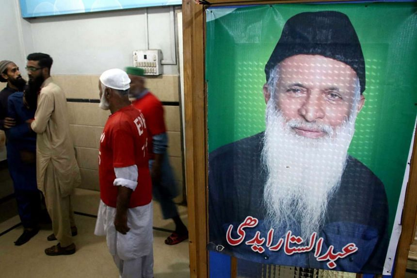 Edhi Foundation workers stand next to a portrait of their organisation's founder Abdul Sattar Edhi as they await the arrival of his corpse to the mortuary, in Karachi.