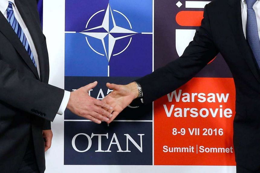 Polish Foreign Minister Witold Waszczykowski (left) and NATO Secretary General Jens Stoltenberg shake hands in front of the logo for the 2016 NATO summit.
