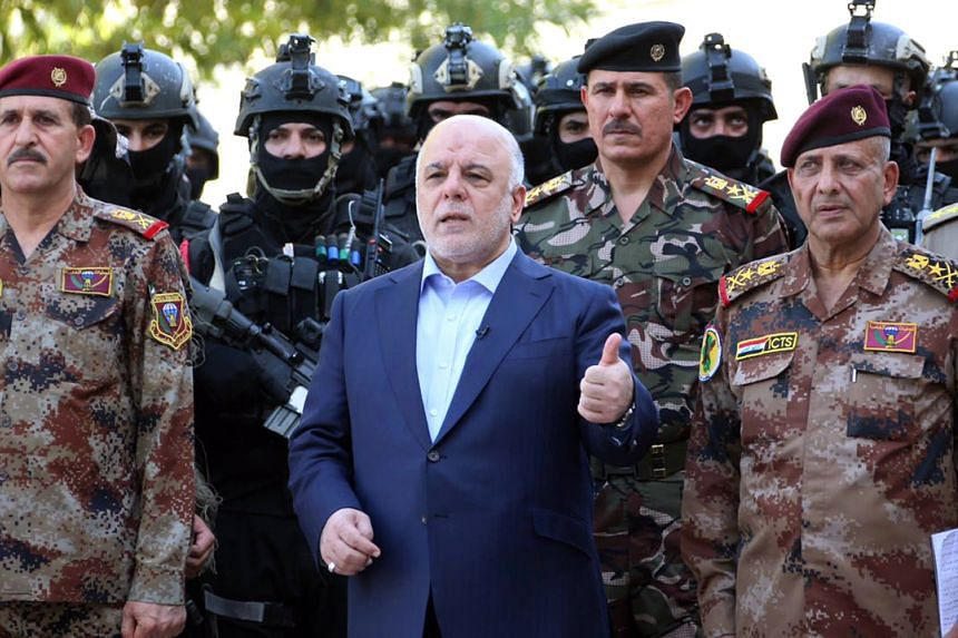 Iraqi Prime Minister Haider al-Abadi (centre) poses for a picture with army generals and members of the counter-terrorism forces in the capital Baghdad.