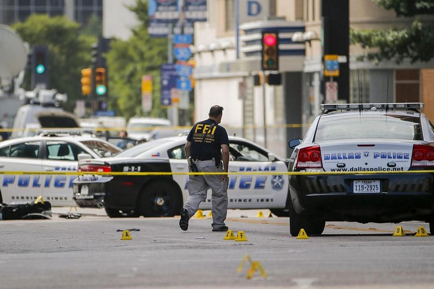 Members of a Federal Bureau of Investigation evidence team continue to work at the scene after the ambush shooting of police officers in Dallas, Texas, on July 9.