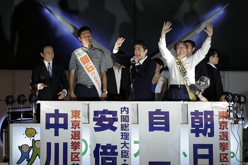 Japan's PM Shinzo Abe (second, right) and president of the Liberal Democratic Party gestures as he speaks, while Japan's deputy PM and finance minister Taro Aso (far left), and party candidates react during a campaign event in Tokyo, Japan, on July 9