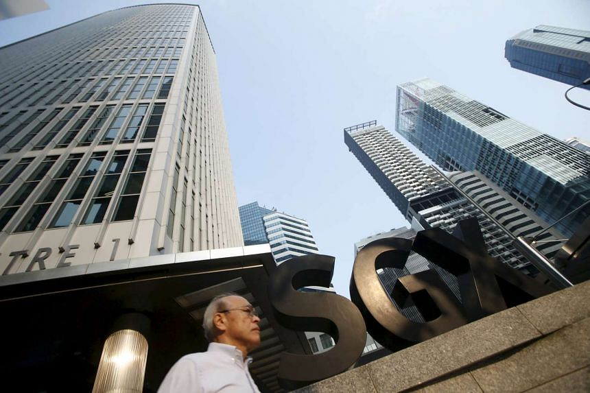 A man passes the SGX building in Singapore's central business district on March 24, 2016.