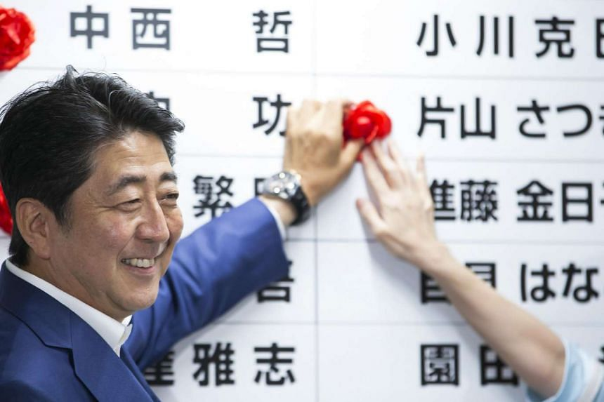 Shinzo Abe, Japan's PM and president of the Liberal Democratic Party, places a red paper rose on a LDP candidate's name to indicate an upper house election victory at the party's headquarters in Tokyo, Japan, on July 10.