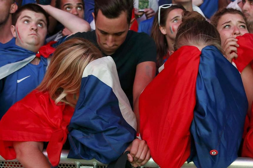 French fans react after France lost to Portugal in the Euro 2016 final football match.