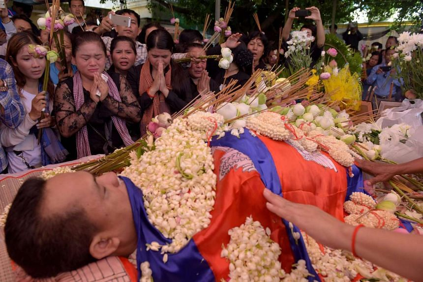Cambodians pay their respects during the funeral ceremony of political analyst Kem Ley at a pagoda in Phnom Penh on July 11.