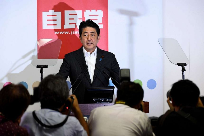 Japanese Prime Minister Shinzo Abe prior to a press conference at his ruling Leberal Democratic Party headquarters in Tokyo on July 11, 2016.