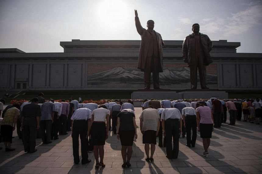 People bow as they pay their respects to the statues of former North Korean leaders Kim Il Sung and Kim Jong Il, at Mansu hill in Pyongyang, on July 7, 2016.