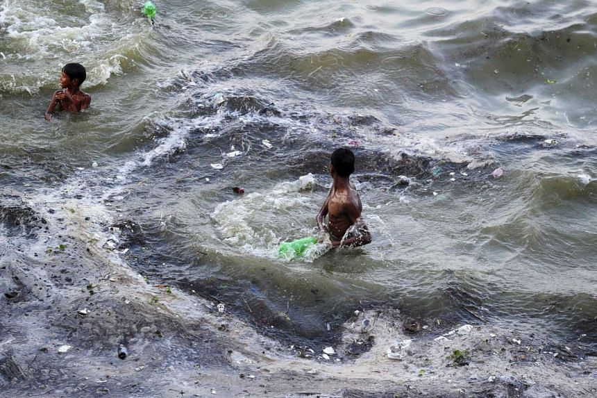 Indian youths play in flood waters after the level of the river Ganges rose following heavy monsoon rains in Allahabad on July 10, 2016.