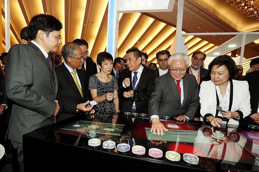 President Tan engaging with a multitouch Smart Table at the opening of the World Cities Summit, Singapore International Water Week and CleanEnviro Summit Singapore. With him are (from left) National Development Minister Lawrence Wong, Environment and