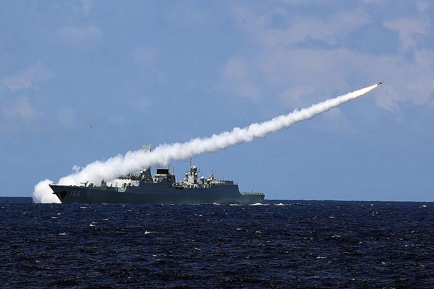 "China's missile destroyer Guangzhou launching an air-defence missile during the military drills in the South China Sea last week. The drills focused on ""air-control operations, sea battles and anti-submarine warfare"", said the PLA Daily, the Chinese"